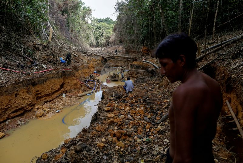 FILE PHOTO: A Yanomami indian follows agents of Brazil's environmental agency in a gold mine during an operation against illegal gold mining on indigenous land, in the heart of the Amazon rainforest