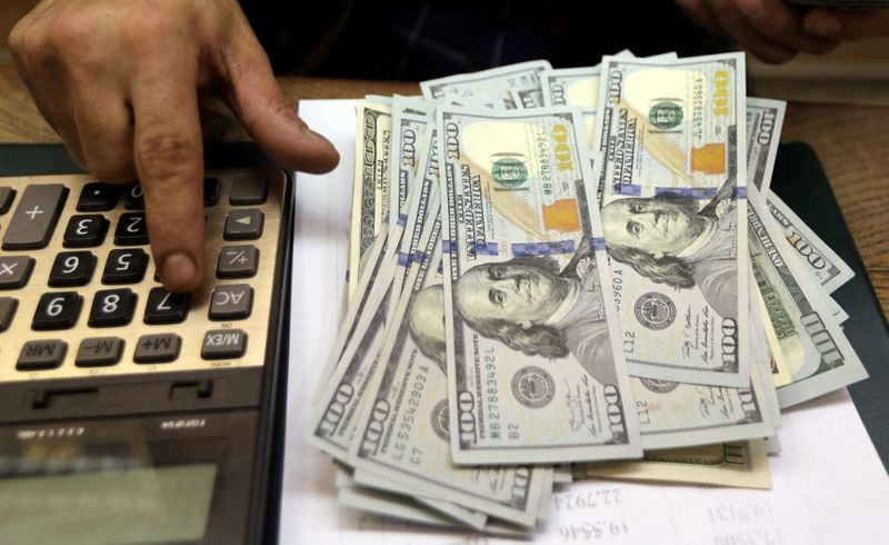 FILE PHOTO: An employee counts U.S. dollar bills at a money exchange office in central Cairo