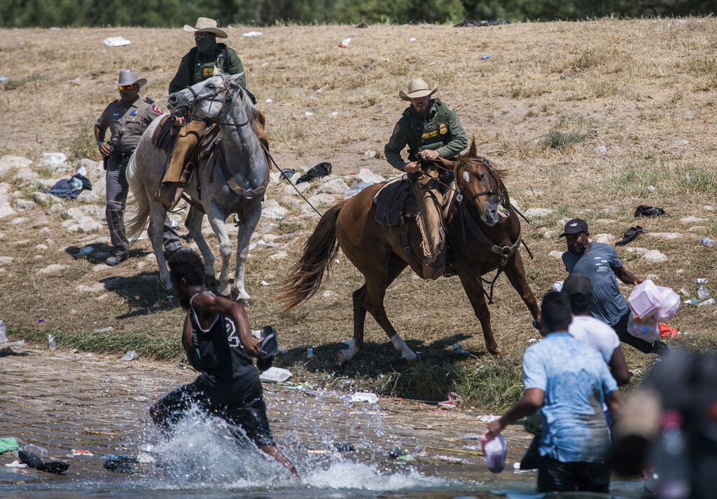 U.S. Customs and Border Protection mounted officers attempt to contain migrants as they cross the Rio Grande from Ciudad Acuna, Mexico, into Del Rio, Texas, Sunday, Sept. 19, 2021. Criticism has been fueled by the images that went viral this week of Border Patrol agents on horseback using aggressive tactics against the migrants. (AP Photo/Felix Marquez)