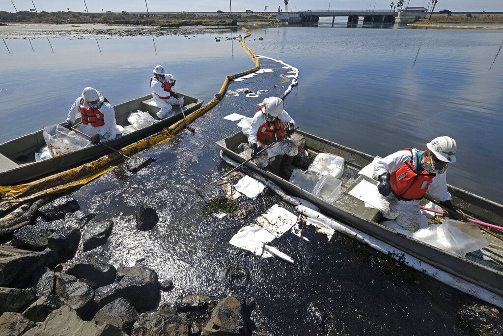 Cleanup contractors deploy skimmers and floating barriers known as booms to try to stop further oil crude incursion into the Wetlands Talbert Marsh in Huntington Beach, Calif., Sunday, Oct. 3, 2021. (AP Photo/Ringo H.W. Chiu)