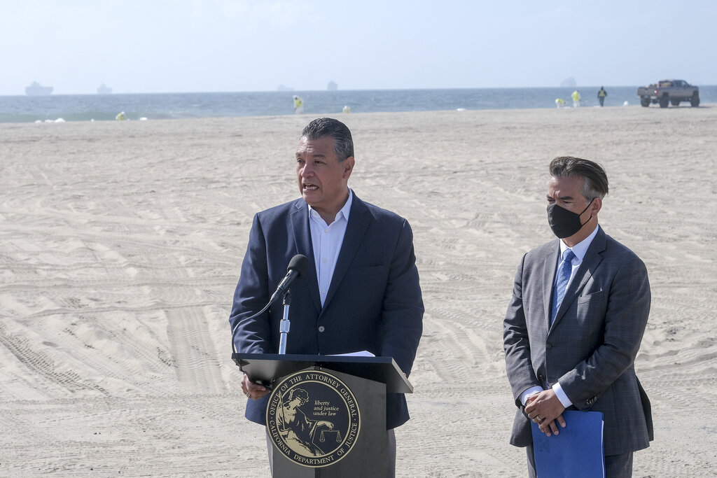 U.S. Sen. Alex Padilla, D-Calif., left, answers questions accompanied by California Attorney General Rob Bonta in a news conference on a beach in Huntington Beach, Calif., Monday, Oct. 11, 2021. Huntington Beach reopened its shoreline this morning after water testing results came back with non-detectable amounts of oil associated toxins in ocean water, city officials and California State Parks announced. (AP Photo/Ringo H.W. Chiu)
