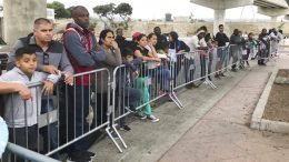 """FILE - In this Sept. 26, 2019, file photo asylum seekers in Tijuana, Mexico, listen to names being called from a waiting list to claim asylum at a border crossing in San Diego. The Biden administration outlined a plan to reinstate a border policy that made asylum-seekers wait in Mexico for hearings in U.S. immigration court. Details were disclosed in a court filing after a federal judge in Texas ordered that the policy by resumed """"in good faith,"""" having started under President Donald Trump and sending about 70,000 people back to Mexico until Biden abruptly ended because he felt it was inhumane.(AP Photo/Elliot Spagat, File)"""