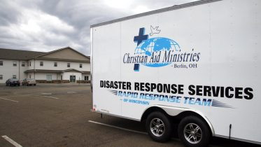This Sunday, Oct. 17, 2021 photo shows the logo for Christian Aid Ministries in Berlin, Ohio, on a vehicle. A group of 17 missionaries including children has been kidnapped by a gang in Haiti, according to a voice message sent to various religious missions by the organization. The message from Ohio-based Christian Aid Ministries said the missionaries were on their way home from building an orphanage. (AP Photo/Tom E. Puskar)