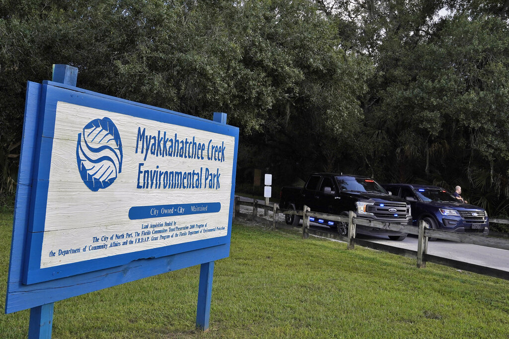 North Port, Fla., police officer block the entrance to the Myakkahatchee Creek Environmental Park Wednesday, Oct. 20, 2021, in North Port, Fla. Items believed to belong to Brian Laundrie and potential human remains were found in a Florida wilderness park during a search for clues in the slaying of Gabby Petito . (AP Photo/Chris O'Meara)