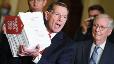 US Senator John Barrasso, Republican of Wyoming, with Senators Mitch McConnell (R), and John Thune (L, rear),holds a copy of the reconciliation bill as he speaks after the Republican policy luncheon at the US Capitol in Washington, DC on September 28, 2021. (Photo by MANDEL NGAN / AFP) (Photo by MANDEL NGAN/AFP via Getty Images)