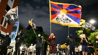 Demonstrators hold the flags of Tibet (C) and 'Free Hong Kong - Revolution Now' (L) during an anti-China rally outside the Parliament in Taipei on October 1, 2021. (Photo by Sam Yeh / AFP) (Photo by SAM YEH/AFP via Getty Images)