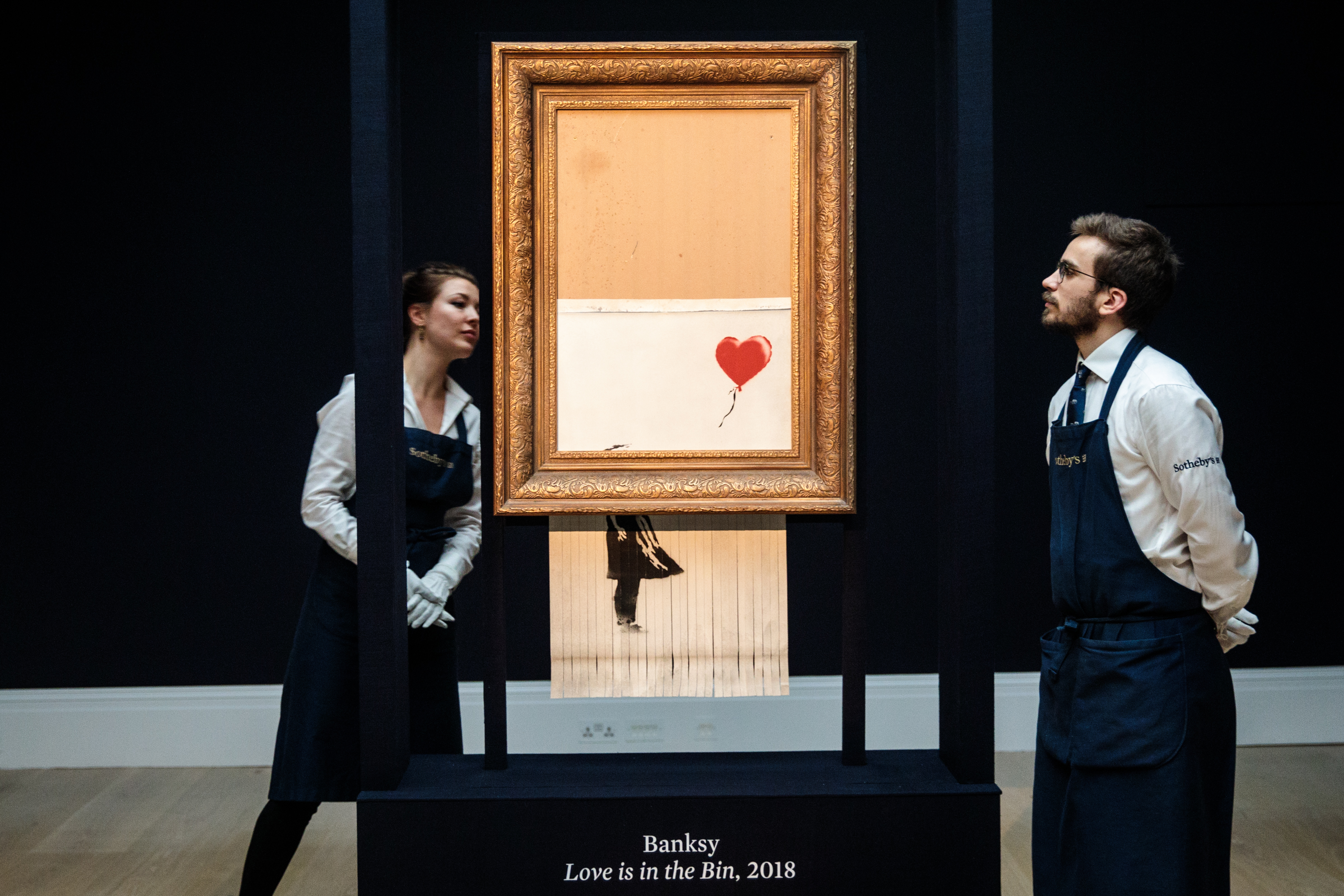 Sotheby's employees view 'Love is in the Bin' by British artist Banksy during a media preview at Sotheby's auction house in London, United Kingdom. (Photo by Jack Taylor/Getty Images)