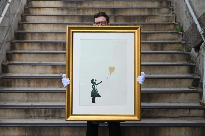 An employee of auction house Christie's poses with 'Girl with Balloon' (Gold) by British street artist Banksy at the Southbank centre, in London. (DANIEL LEAL-OLIVAS/AFP via Getty Images)