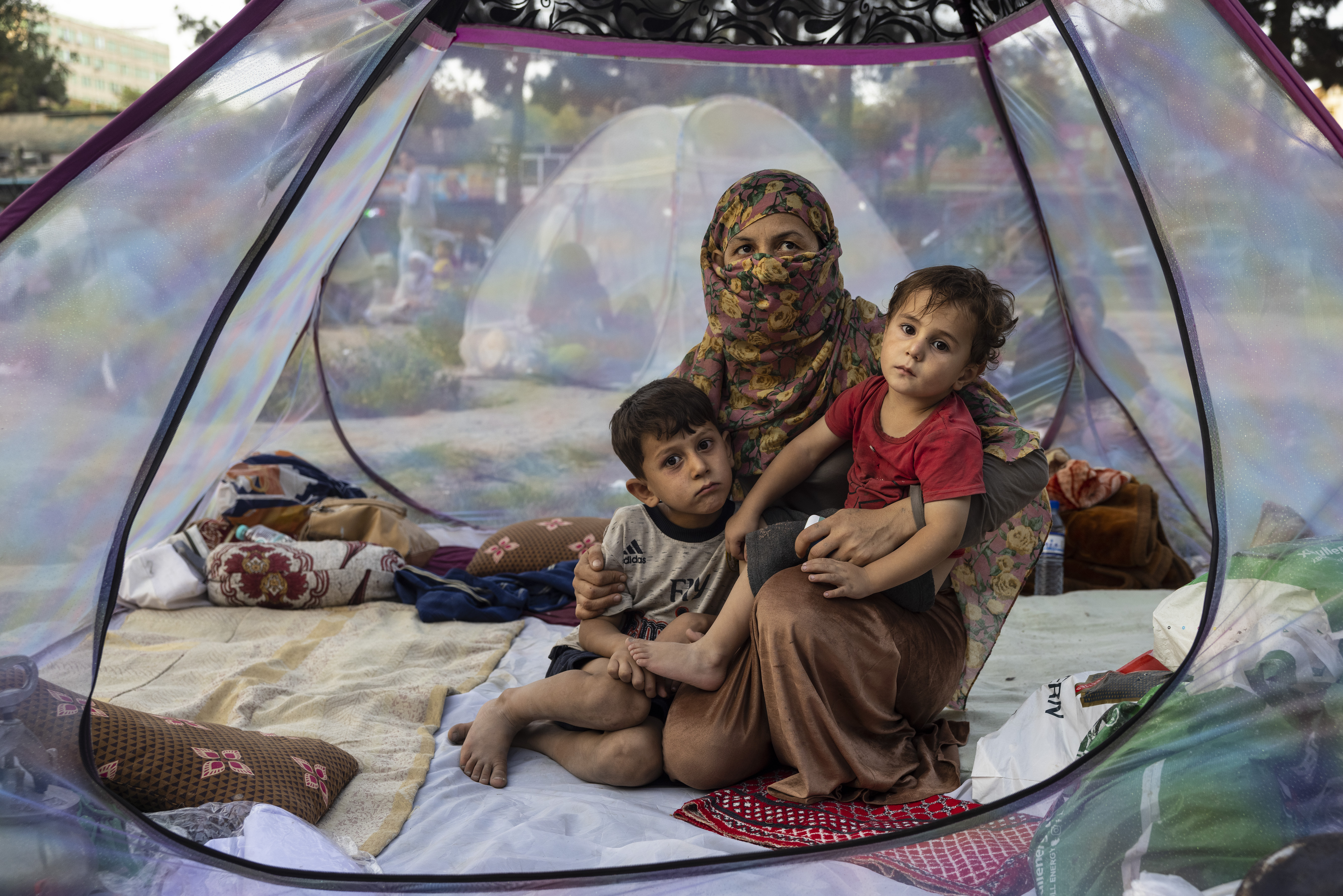 Farzia, 28, who lost her husband in Baghlan one week ago to fighting by the Taliban sits with her children, Subhan, 5, and Ismael ,2, in a tent at a makeshift IDP camp in Share-e-Naw park to various mosques and schools on August 12, 2021 in Kabul, Afghanistan. People displaced by the Taliban advancing are flooding into the Kabul capital to escape the Taliban takeover of their provinces. (Photo by Paula Bronstein/Getty Images)