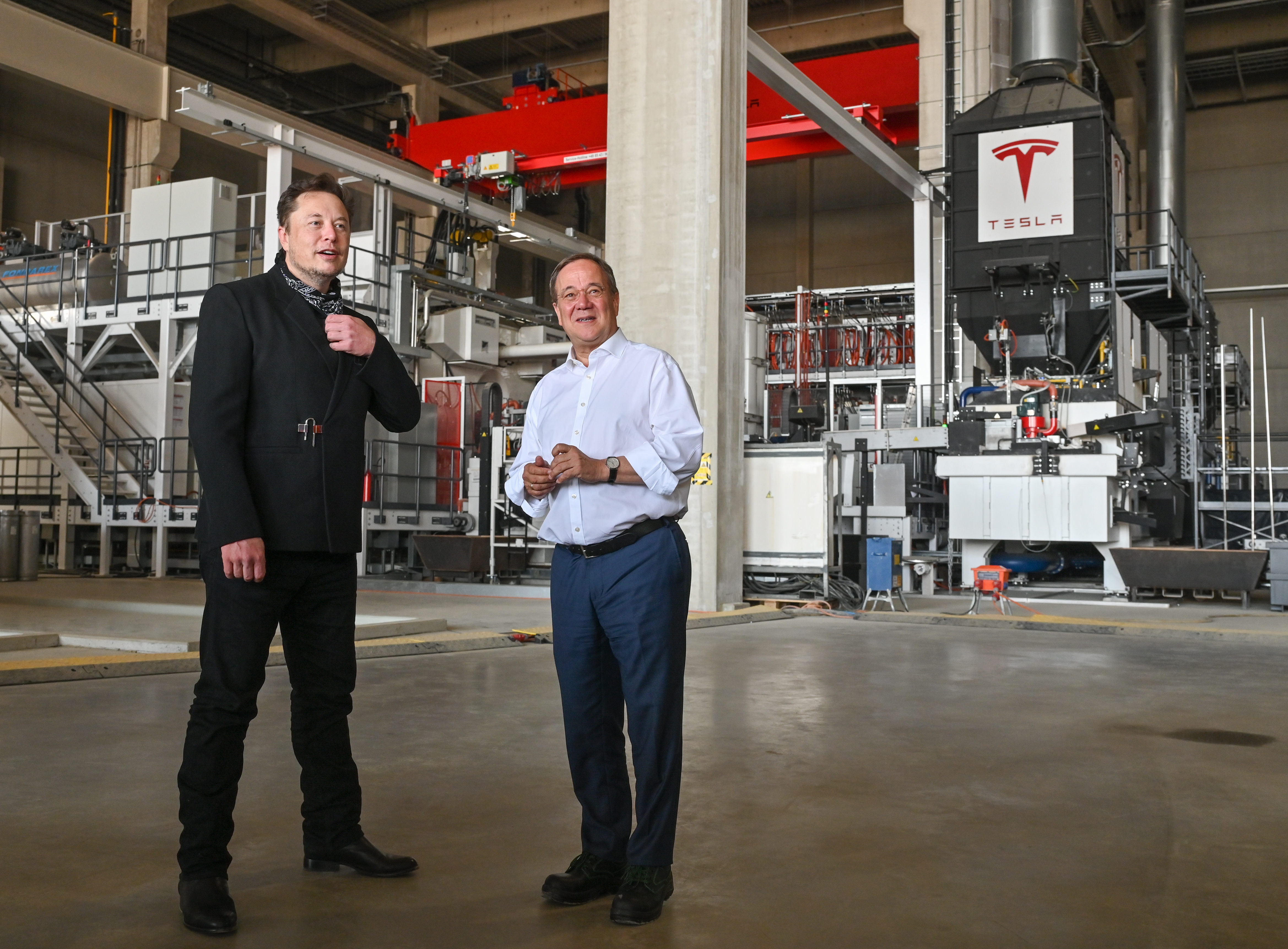 Tesla CEO Elon Musk and Armin Laschet, CDU Federal Chairman and Prime Minister of North Rhine-Westphalia, talk during a tour of the plant of the future foundry of the Tesla Gigafactory on August 13, 2021 in Grünheide near Berlin, Germany. The US company plans to build around 500,000 of the compact Model 3 and Model Y series here every year. (Photo by Patrick Pleul - Pool/Getty Images)