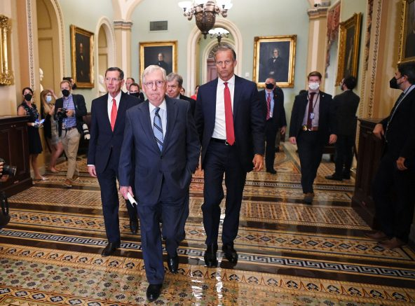 U.S. Senate Minority Leader Mitch McConnell, Republican of Kentucky, with Republican Senators John Barrasso (left) and John Thune (right), arrives to speak to reporters after the Republican policy luncheon at the U.S. Capitol in Washington, D.cC) (Photo by MANDEL NGAN/AFP via Getty Images)
