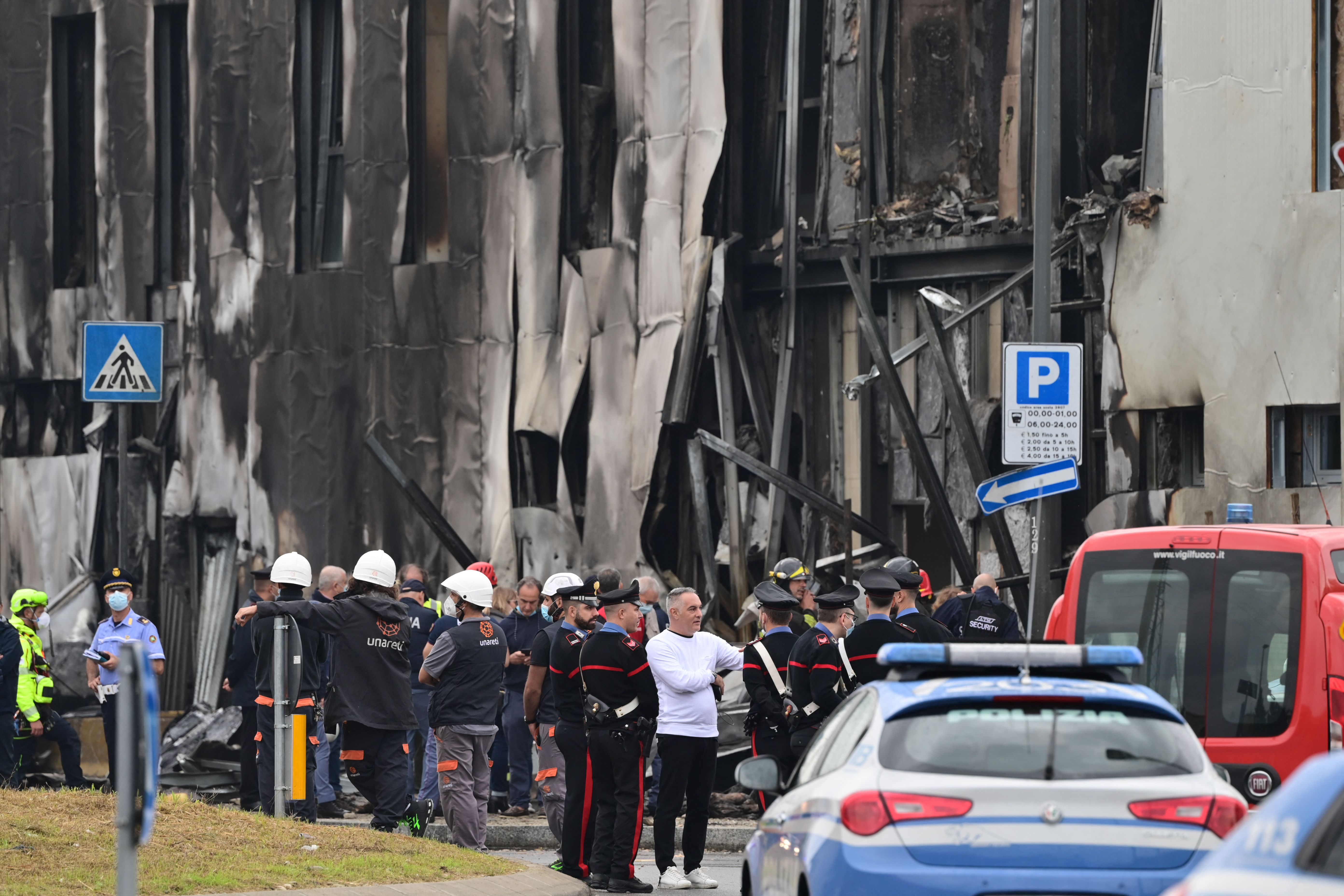 Police and rescue teams stand outside an apparently vacant office building where a small plane carrying five passengers and the pilot crashed in the Milan suburb of San Donato on October 3, 2021. (Photo by MIGUEL MEDINA/AFP via Getty Images)