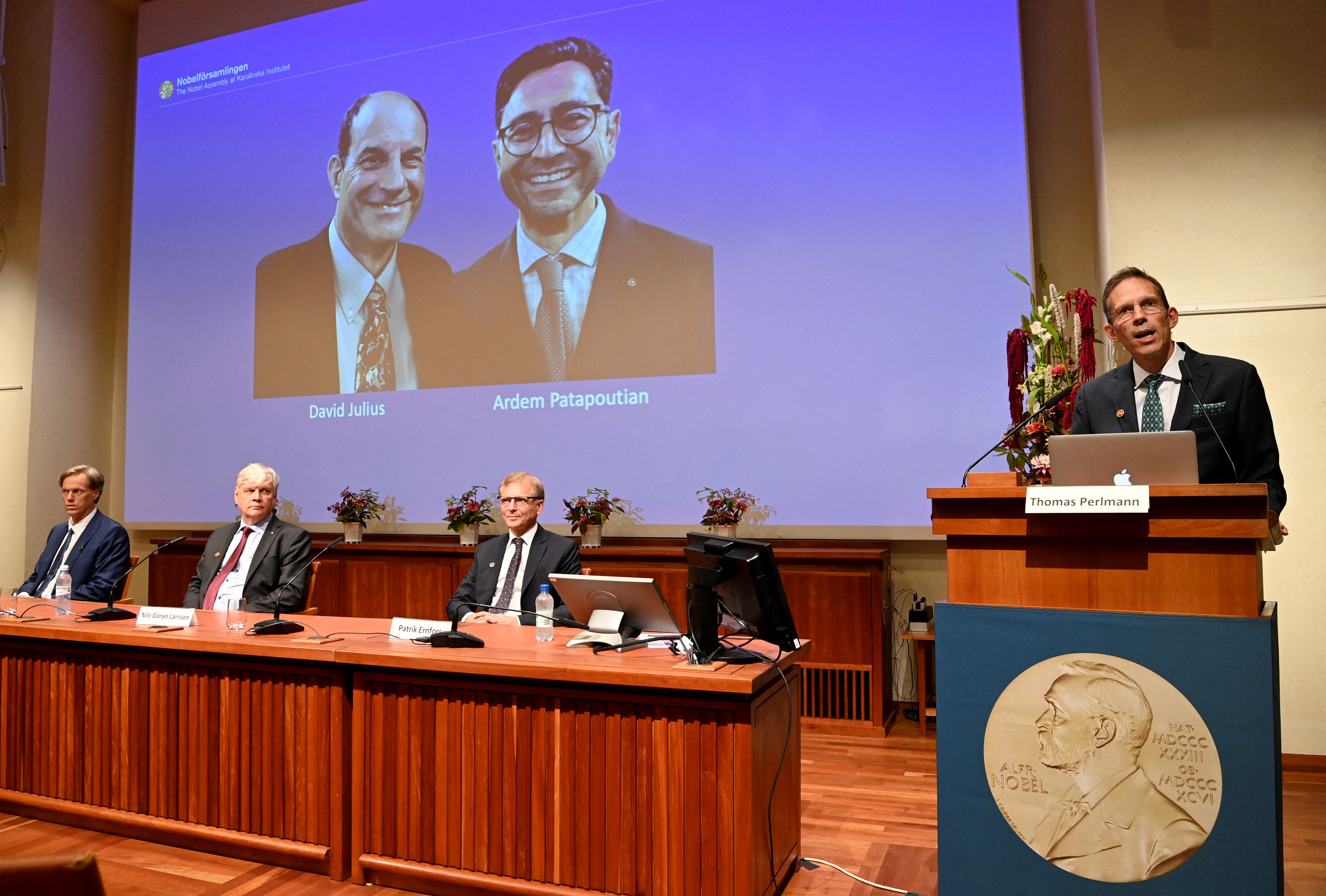 Thomas Perlmann (right), the Secretary of the Nobel Committee, stands next to a screen displaying the winners of the 2021 Nobel Prize in Physiology or Medicine David Julius (left) and Ardem Patapoutian, during a press conference at the Karolinska Institute in Stockholm, Sweden, on October 4, 2021. - US scientists David Julius and Ardem Patapoutian won the Nobel Medicine Prize for discoveries on receptors for temperature and touch. (Photo by JONATHAN NACKSTRAND/AFP via Getty Images)