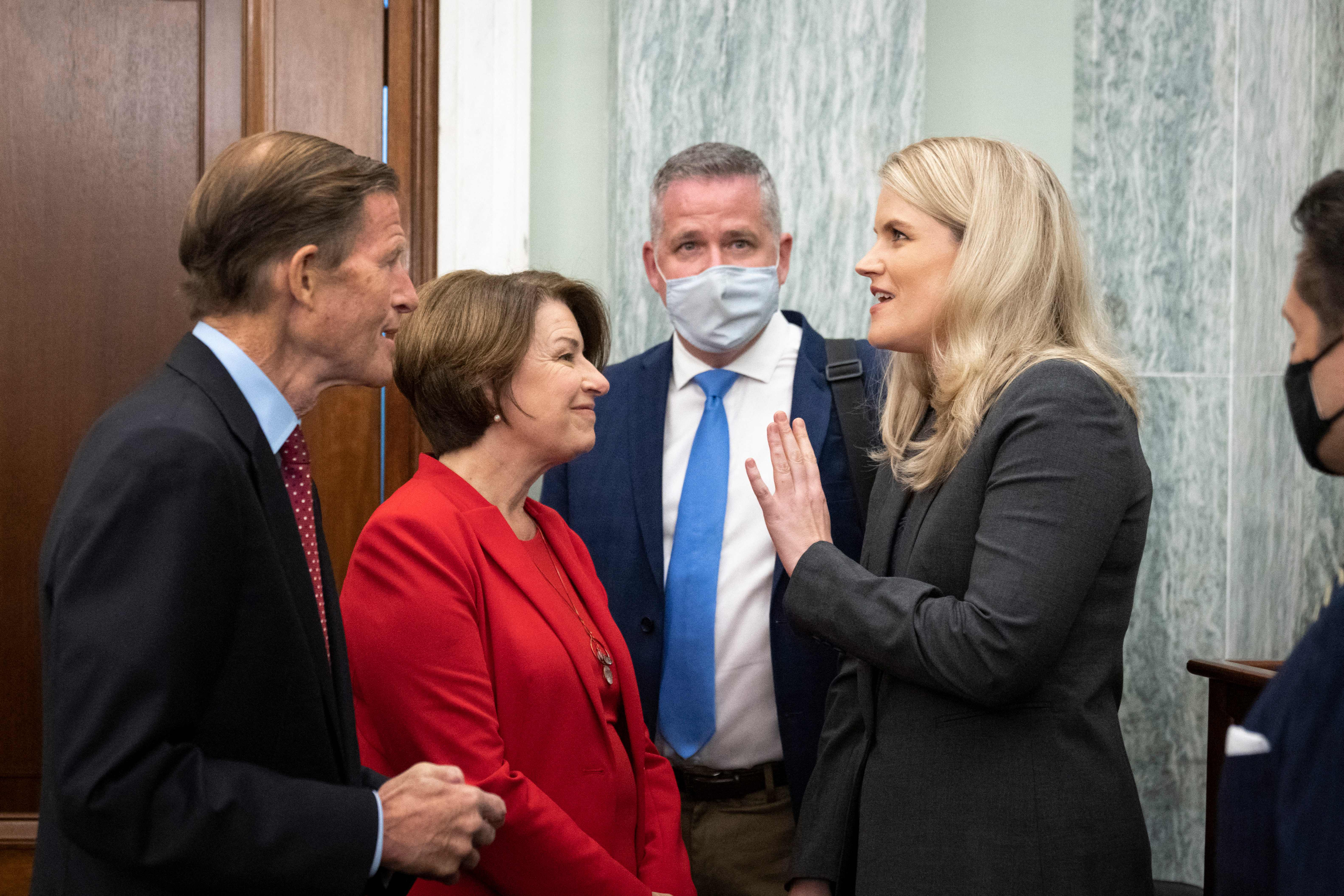 Former Facebook employee and whistleblower Frances Haugen (right) is welcomed by US Senators Richard Blumenthal (left) and Amy Klobuchar (2nd left) as she arrives to testify during a Senate Committee on Commerce, Science, and Transportation hearing on Capitol Hill, October 5, 2021, in Washington, DC. (Photo by DREW ANGERER/POOL/AFP via Getty Images)