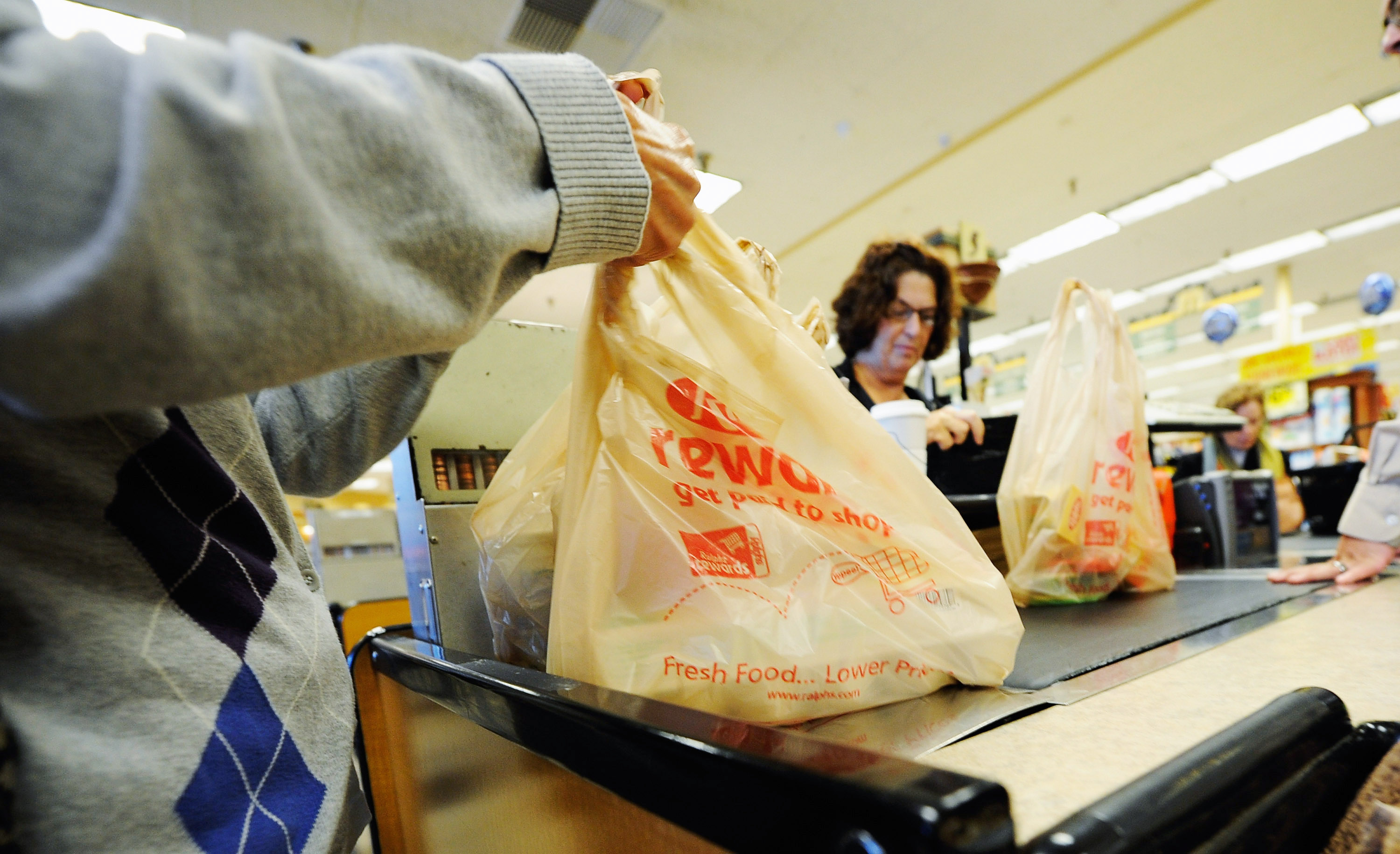 Customers of Ralphs supermarket use plastic bags to carry their groceries home in Glendale, California.(Photo by Kevork Djansezian/Getty Images)