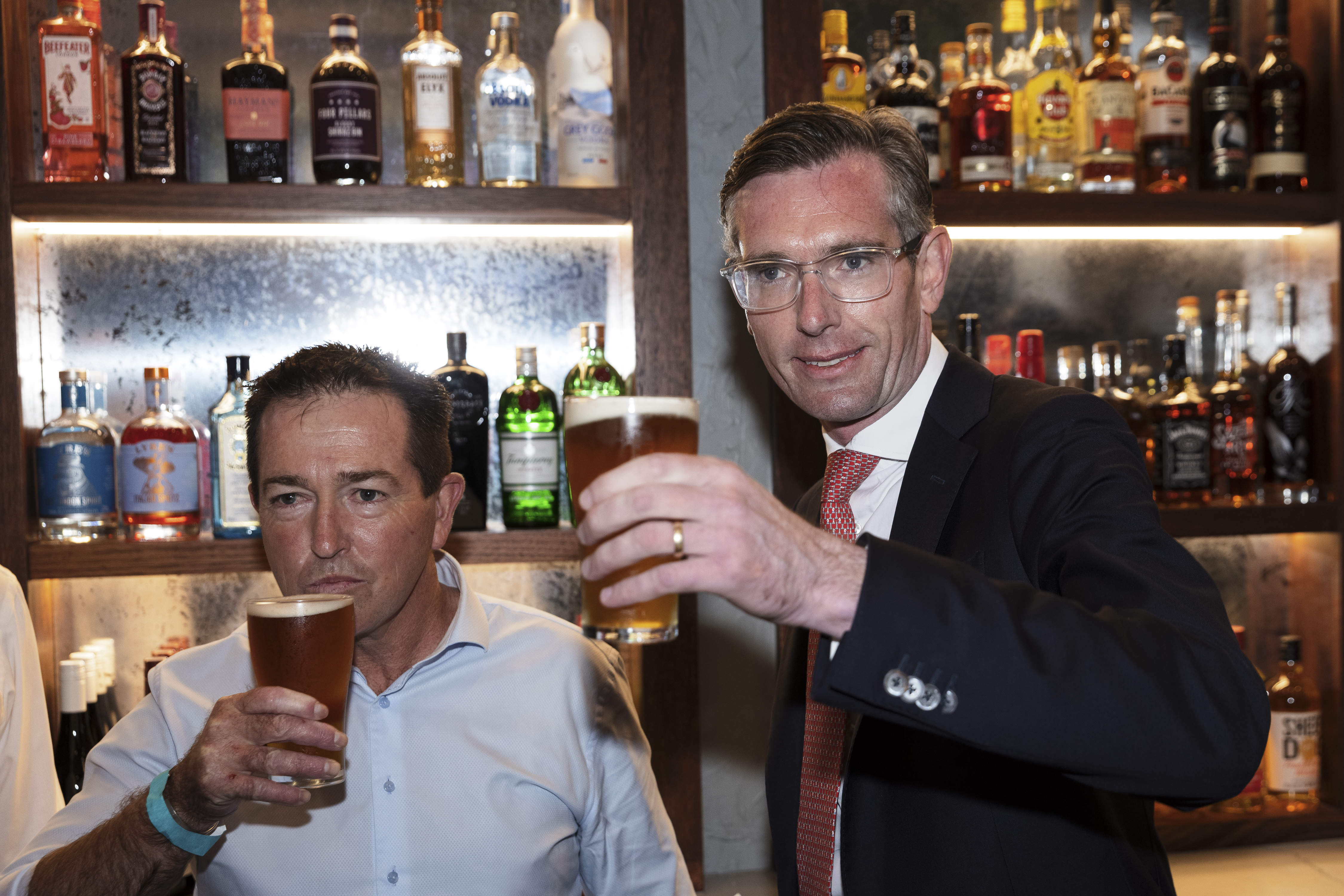 Premier Dominic Perrottet (right) and Deputy Premier Pail Toole drink a beer before holding a media conference at Watson's Pub in Moore Park on October 11, 2021 in Sydney, Australia. (Photo by Brook Mitchell/Getty Images)