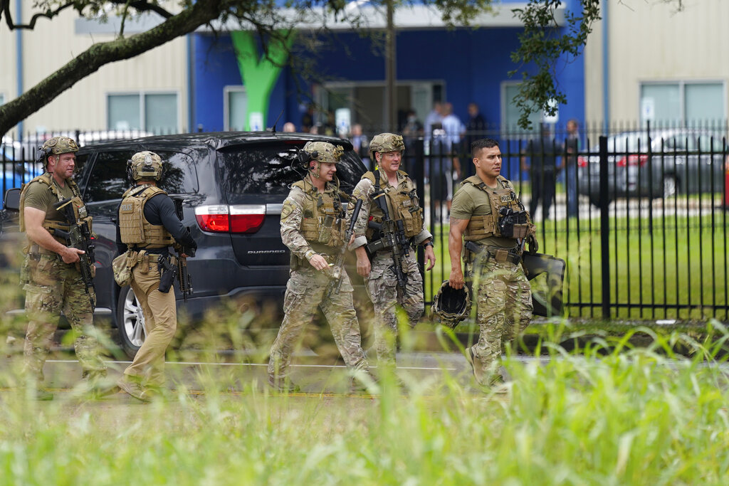 Members of the Houston Police SWAT team walk down the road outside YES Prep Southwest Secondary school after a shooting on Friday, Oct. 1, 2021 in Houston. An employee at the Houston charter school was shot and wounded by a former student, police said. Houston Police Chief Troy Finner said a 25-year-old man surrendered after being surrounded by police. (AP Photo/David J. Phillip)