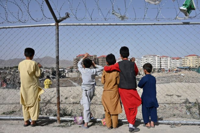TOPSHOT - Children watch people at a camp for internally displaced people (IDP) where new apartment buildings are located in Kabul on June 21, 2021. (Photo by ADEK BERRY / AFP) (Photo by ADEK BERRY/AFP via Getty Images)