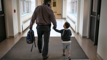 STAMFORD, CONNECTICUT - SEPTEMBER 16: Assistant principal Joe Claps escorts a child to class at Stark Elementary School on September 16, 2020 in Stamford, Connecticut. Most students at Stamford Public Schools are taking part in a hybrid education model, where they attend in-school classes every other day and distance learn the rest. About 20 percent of students in the school district, however, are enrolled in the distance learning option due to coronavirus concerns. (Photo by John Moore/Getty Images)