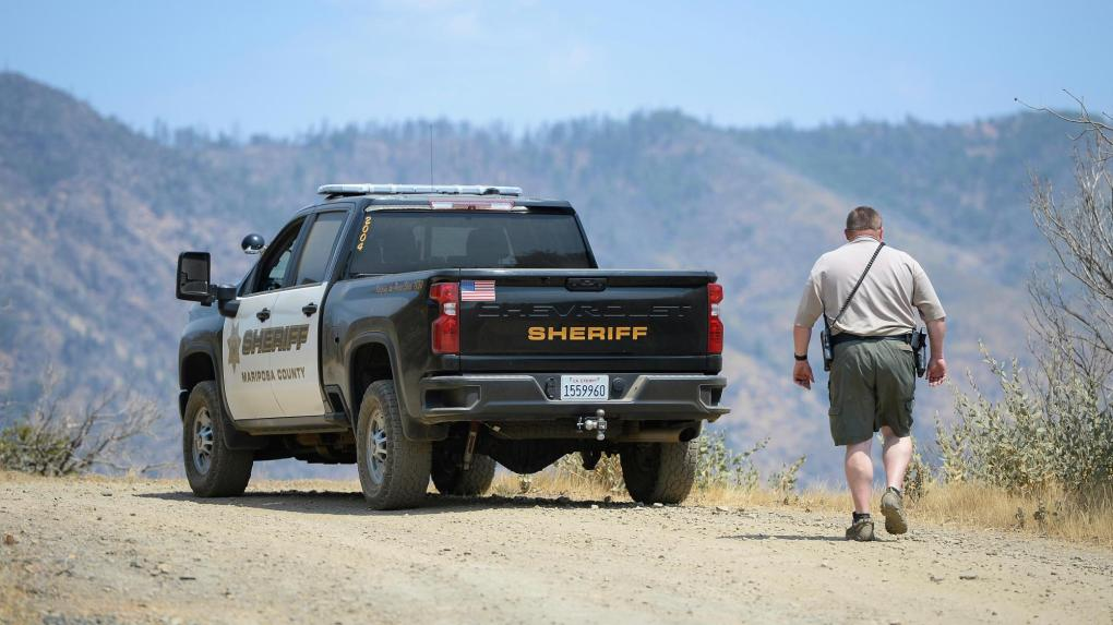 A Mariposa County deputy sheriff stands watch over a remote area northeast of the town of Mariposa, Calif., on Wednesday, Aug. 18, 2021, near the area where a family and their dog were reportedly found dead the day before. Investigators are considering whether toxic algae blooms or other hazards may have contributed to the deaths of the Northern California couple, their baby and the family dog on a remote hiking trail, authorities said. (Craig Kohlruss/The Fresno Bee via AP)