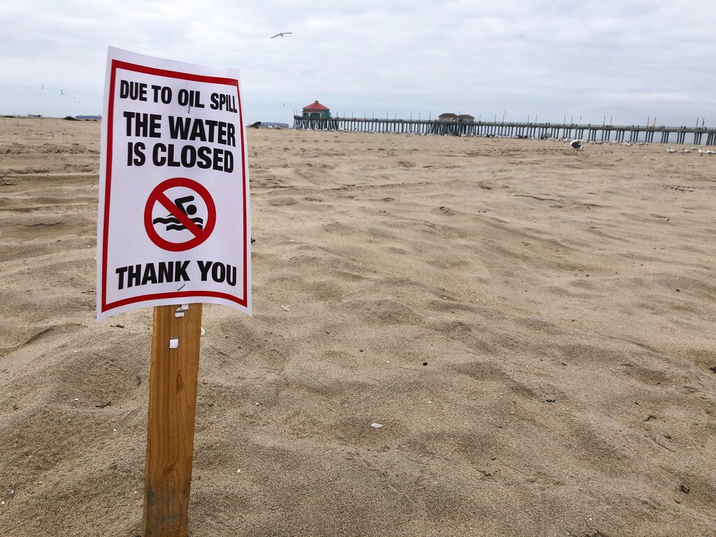 Signs warn that beaches are closed to swimmers and surfers due to the recent oil spill in Huntington Beach, Calif., Wednesday Oct. 6, 2021. Officials imposed restrictions on Southern California beaches in response to a leak in an oil pipeline that sent over 126, 000 gallons of oil into the ocean and some ending up on nearby beaches. (AP Photo/Stefanie Dazio)