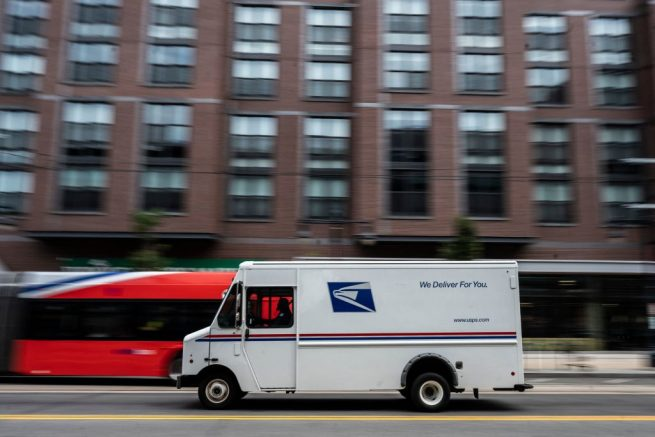 A postman drives a United States Postal service (USPS) mail delivery truck through Washington, DC on August 13, 2021. (Photo by ANDREW CABALLERO-REYNOLDS / AFP) (Photo by ANDREW CABALLERO-REYNOLDS/AFP via Getty Images)