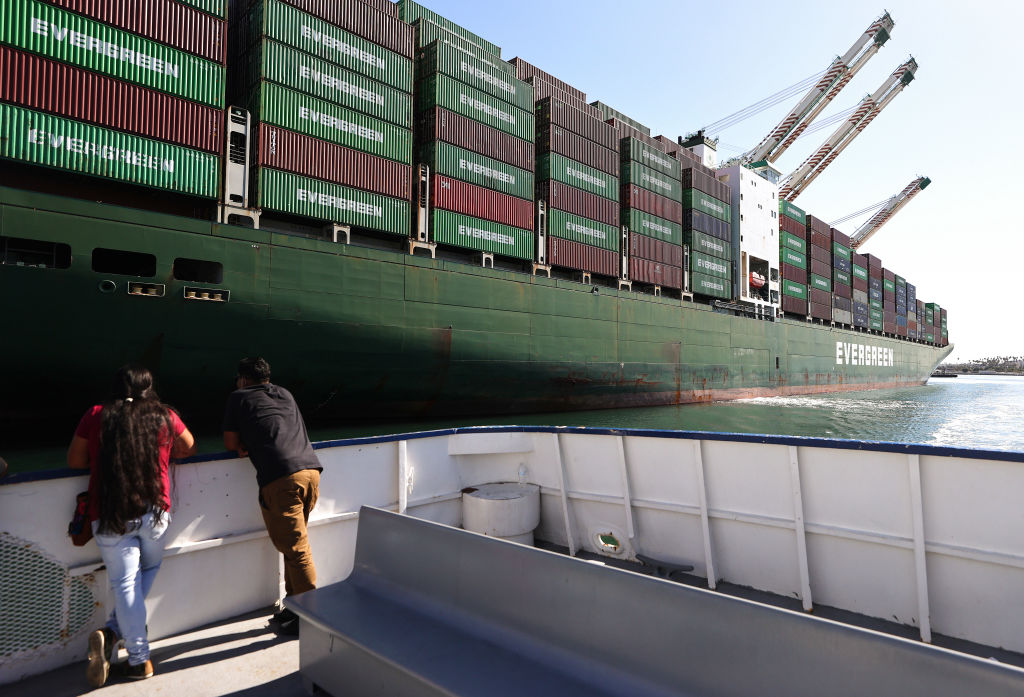 SAN PEDRO, CALIFORNIA - OCTOBER 15: People ride on a tour boat beneath cargo containers stacked on a container ship at the Port of Los Angeles, the nation's busiest container port, on October 15, 2021 in San Pedro, California. As surging inflation and supply chain disruptions are disrupting global economic recovery, the Washington-based IMF has projected that global gross domestic product will grow by 5.9% this year — a 0.1 percentage point lower than its July estimate. The Port of Los Angeles is transitioning to 24/7 operations amid efforts to ease supply backlogs. (Photo by Mario Tama/Getty Images)
