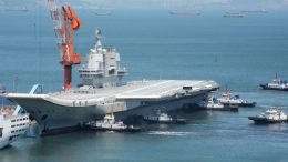 """This photo taken on May 18, 2018 shows tugs guiding China's first domestically manufactured aircraft carrier, known as """"Type 001A"""", as it returns to port in Dalian in China's northeastern Liaoning province after its first sea trial. - China's first domestically manufactured aircraft carrier started sea trials on May 13, 2018 and returned to port in Dalian on May 18. (Photo by - / AFP) / China OUT (Photo credit should read -/AFP via Getty Images)"""