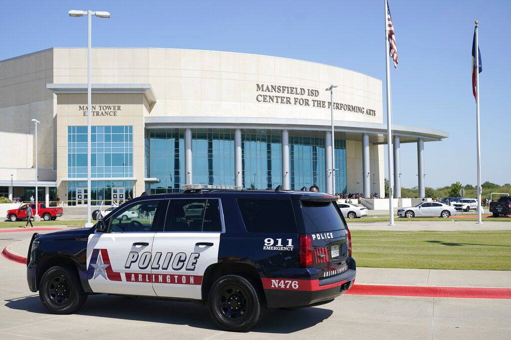 An Arlington, Texas, police vehicle sits outside the Mansfield ISD Center For The Performing Arts Wednesday, Oct. 6, 2021 in Mansfield, Texas, where families were being reunited with their children following a school shooting at Timberview High School in nearby Arlington. (AP Photo/Tony Gutierrez)