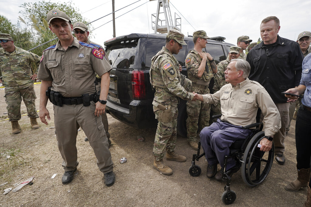 Texas Gov. Greg Abbott, right, shakes a National Guard member's hand after speaking during a news conference along the Rio Grande, Tuesday, Sept. 21, 2021, in Del Rio, Texas. The U.S. is flying Haitians camped in a Texas border town back to their homeland and blocking others from crossing the border from Mexico. (AP Photo/Julio Cortez)