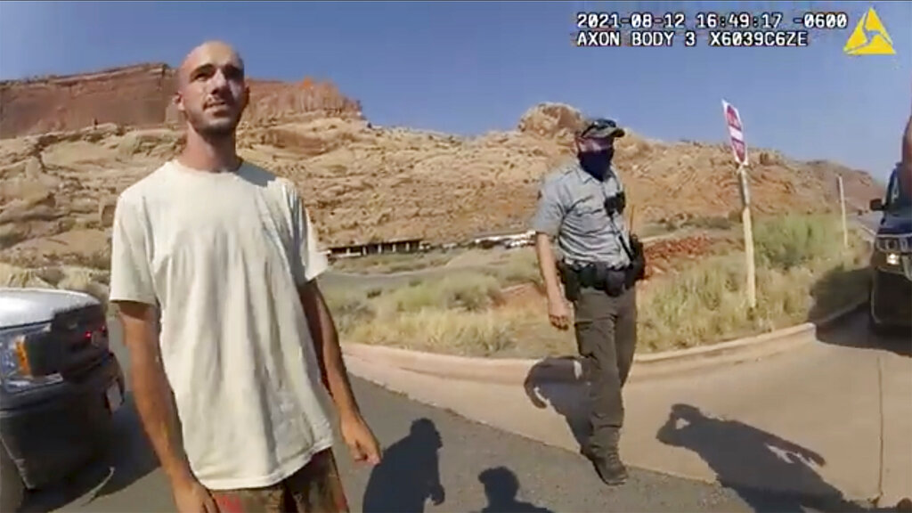 """FILE - This Aug. 12, 2021 file photo from video provided by The Moab Police Department shows Brian Laundrie talking to a police officer after police pulled over the van he was traveling in with his girlfriend, Gabrielle """"Gabby"""" Petito, near the entrance to Arches National Park. Laundrie, the boyfriend of Gabby Petito, whose body was found at a national park in Wyoming after a cross-country trip with him, has been charged with unauthorized use of a debit card as searchers continue looking for him in Florida swampland, federal authorities announced Thursday, Sept. 23, 2021. (The Moab Police Department via AP, File)"""