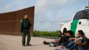 TOPSHOT - A Border Patrol agent apprehends illegal immigrants shortly after they crossed the border from Mexico into the United States on Monday, March 26, 2018 in the Rio Grande Valley Sector near McAllen, Texas. - An estimated 11 million undocumented immigrants live in the United States, many of them Mexicans or from other Latin American countries. (Photo by Loren ELLIOTT / AFP) (Photo credit should read LOREN ELLIOTT/AFP via Getty Images)