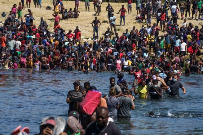 Haitian migrants, part of a group of over 10,000 people staying in an encampment on the US side of the border, cross the Rio Grande river to get food and water in Mexico, after another crossing point was closed near the Acuna Del Rio International Bridge in Del Rio, Texas on September 19, 2021. - The United States said Saturday it would ramp up deportation flights for thousands of migrants who flooded into the Texas border city of Del Rio, as authorities scramble to alleviate a burgeoning crisis for President Joe Biden's administration. (Photo by PAUL RATJE / AFP) (Photo by PAUL RATJE/AFP via Getty Images)