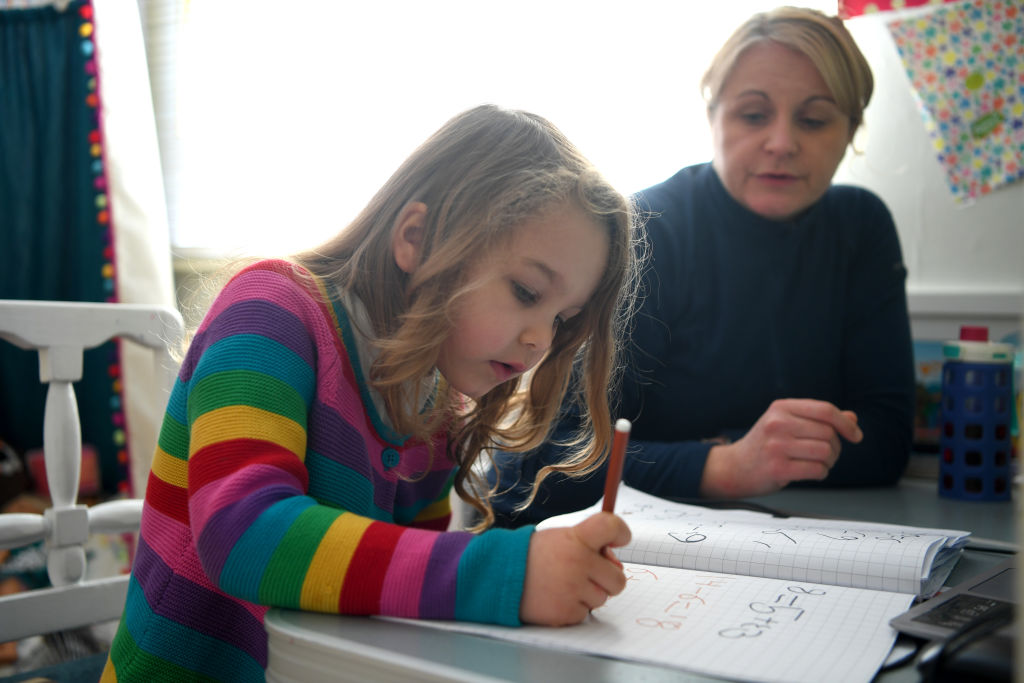 NEWCASTLE-UNDER-LYME, ENGLAND - JANUARY 25: Five-year-old Lois Copley-Jones, who is the photographer's daughter, does her Maths studies in her bedroom on January 25, 2021 in Newcastle-under-Lyme, England. Under current government policy, schools in England wouldn't open before the February half-term break at the earliest, but the Prime Minister has declined to commit to reopening them before Easter. (Photo by Gareth Copley/Getty Images)