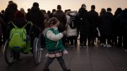 A young girl wearing a protective mask takes a photo with a smartphone at Tiananmen Gate in Beijing on January 23, 2020. - China is halting public transport and closing highway toll stations in two more cities in Hubei province, the epicentre of a deadly virus outbreak, authorities said on January 23. (Photo by NICOLAS ASFOURI / AFP) (Photo by NICOLAS ASFOURI/AFP via Getty Images)